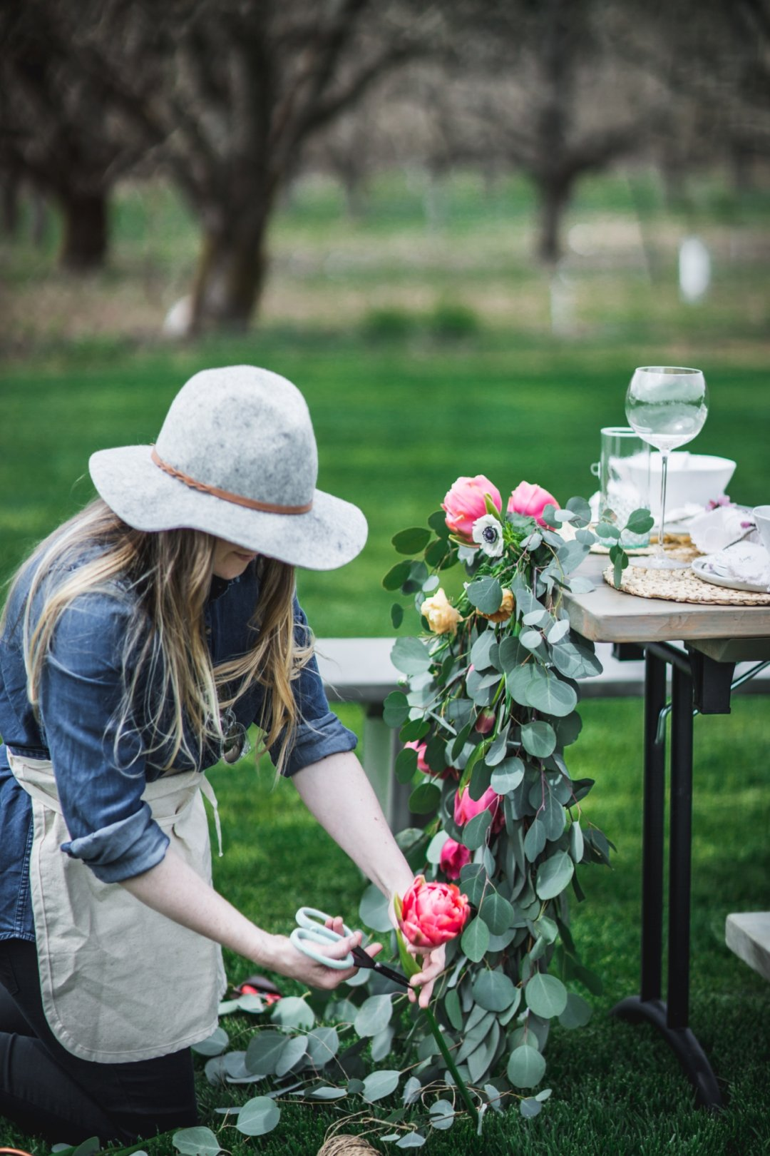 Woman trimming centerpiece wreath and flowers