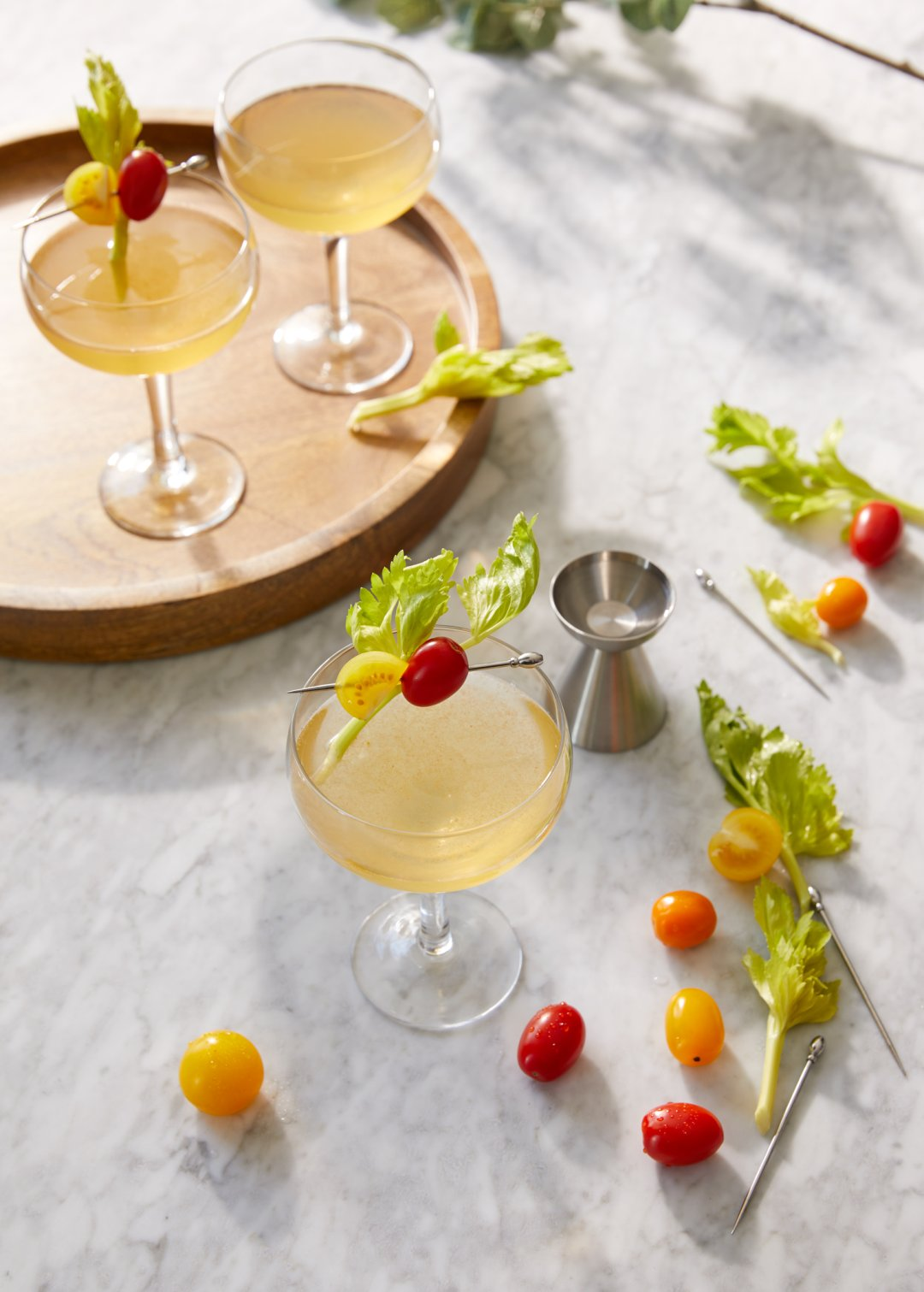 Champagne glasses garnished with halved red and yellow grape tomatoes and small leafy greens on a skewer