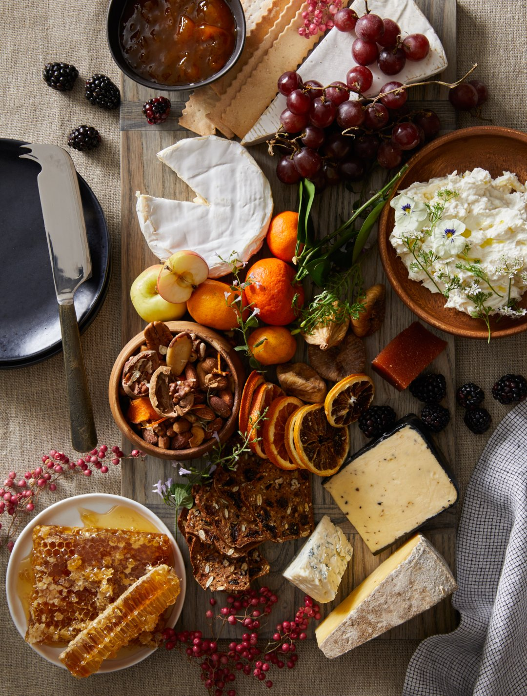 Cheese board with fruit, honey and crackers