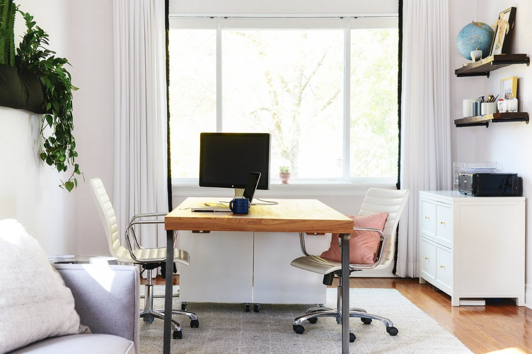 Two white swivel desk chairs on either side of a wood desk in small studio home office space