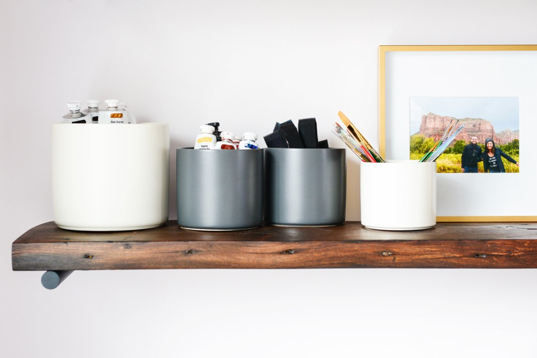 four containers with paint and paint brushes on a wooden shelf next to a scenic photo