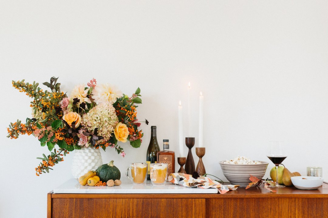 Orange cocktails, popcorn and wine laid out atop a wood sideboard