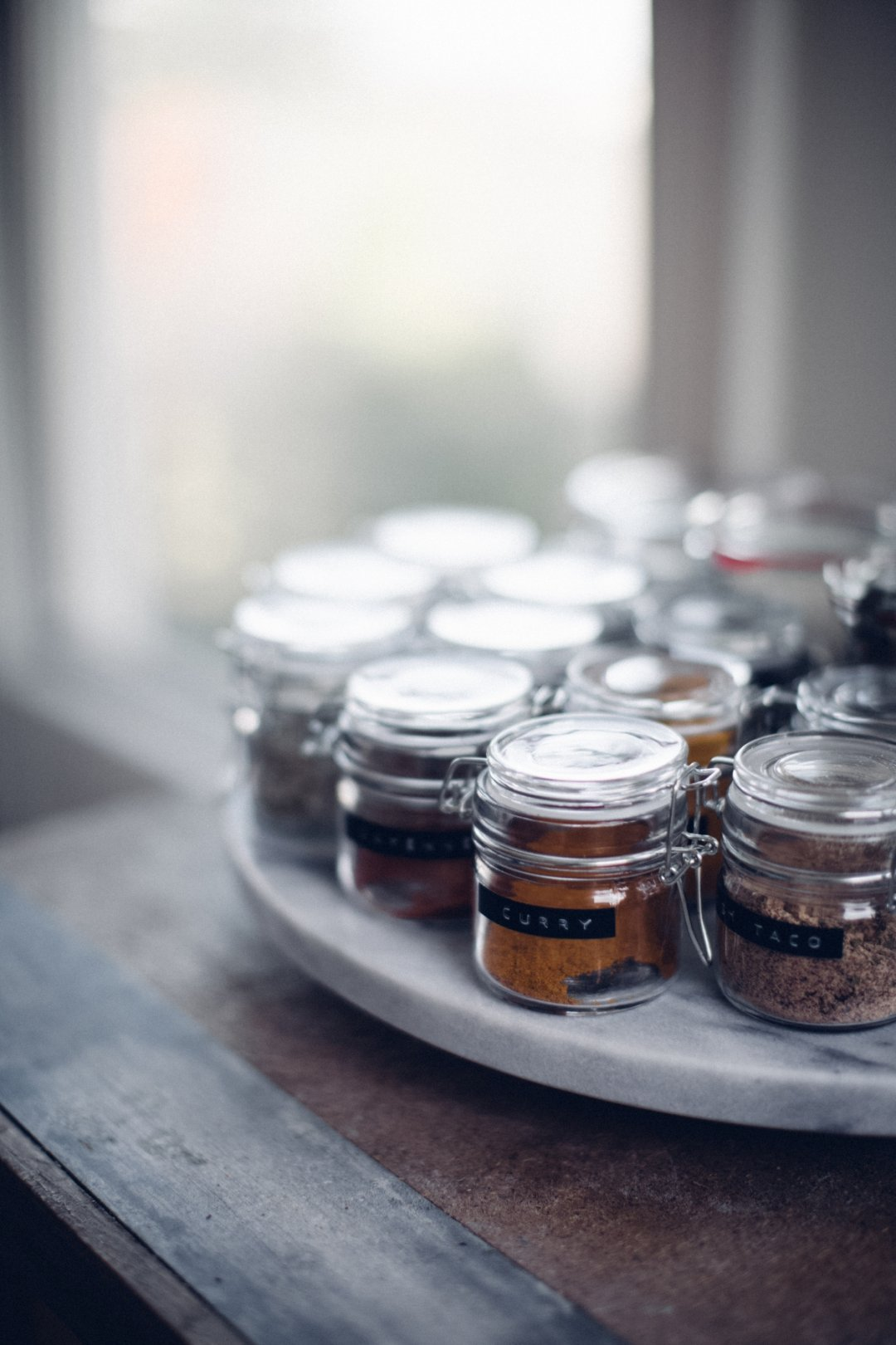 Several mini spice jars with labels on a marble lazy susan