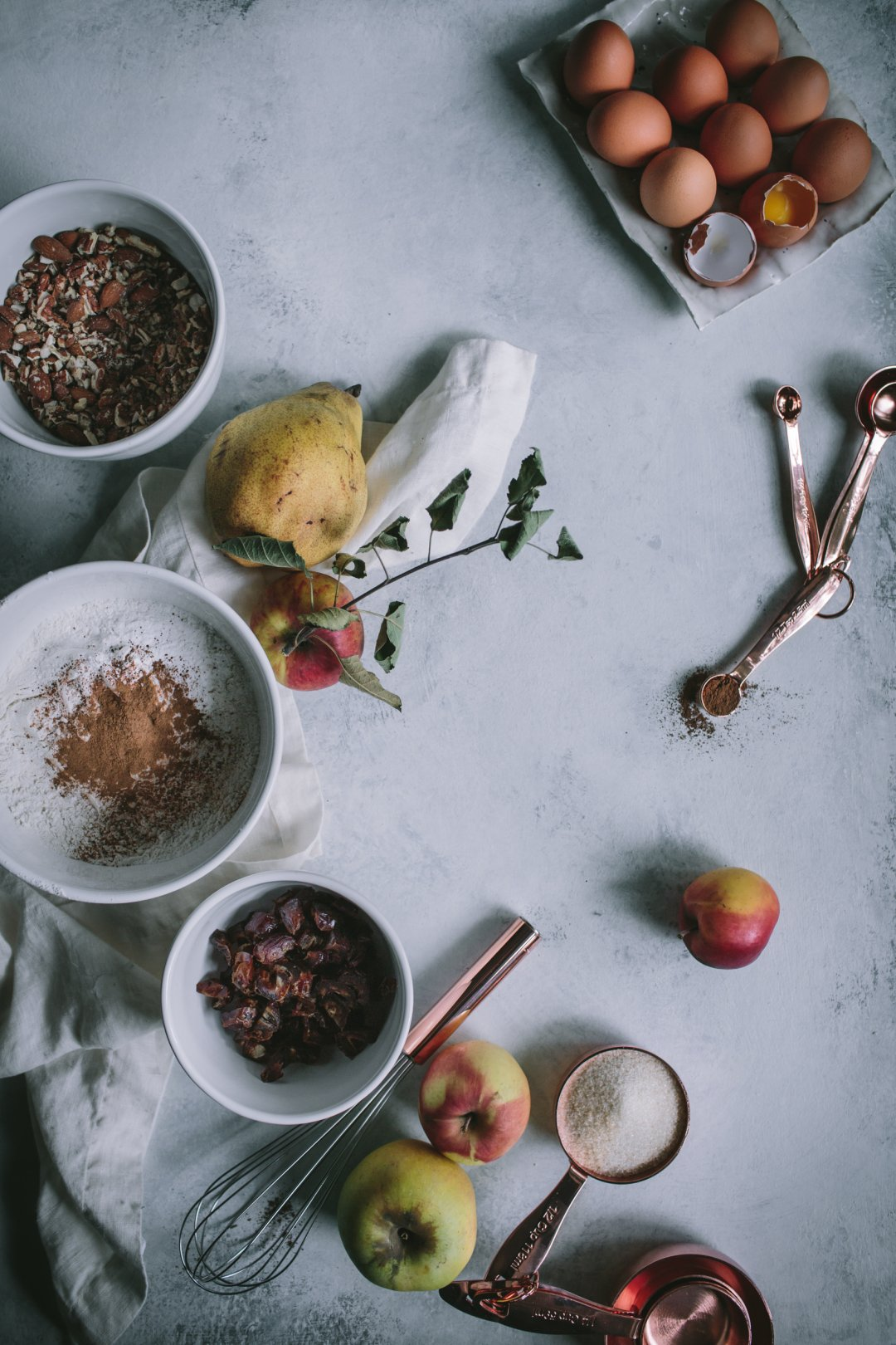 Spread of white mixing bowls and copper measuring cups with muffin ingredients, including flour, dates, chopped nuts, sugar and eggs