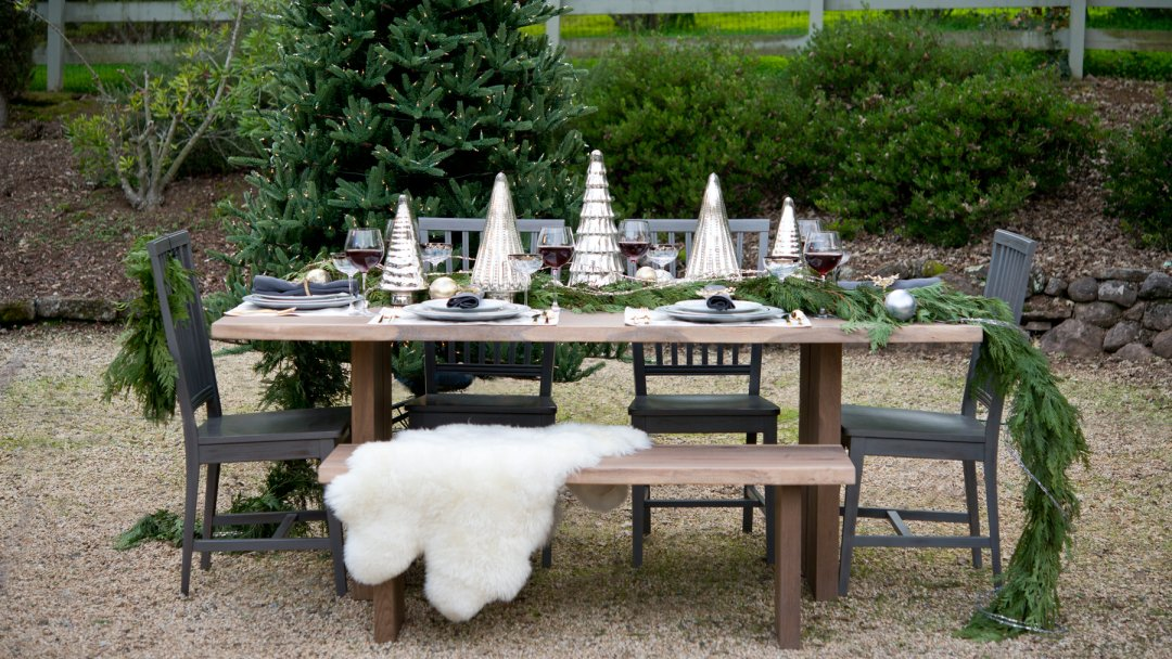 a large table set outside near a christmas tree full of plates wine glasses and tree branches