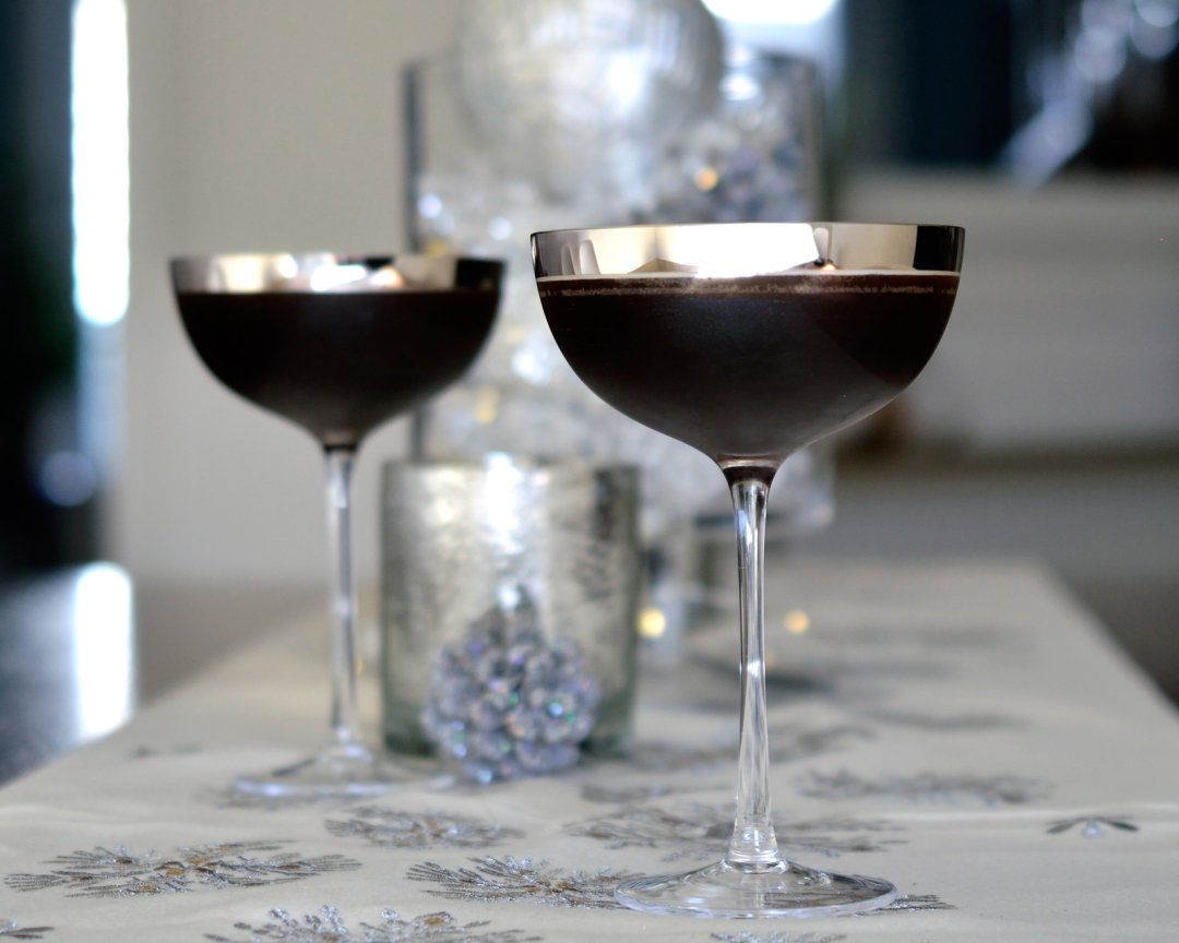 two espresso martinis in glasses on a decorated table