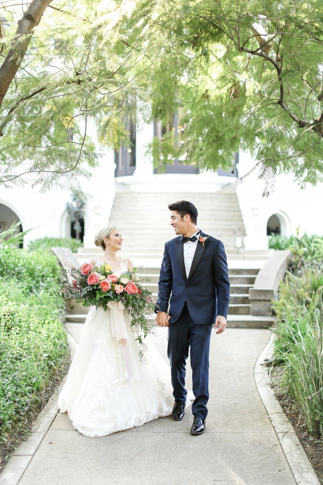 Bride and groom walking hand in hand through garden