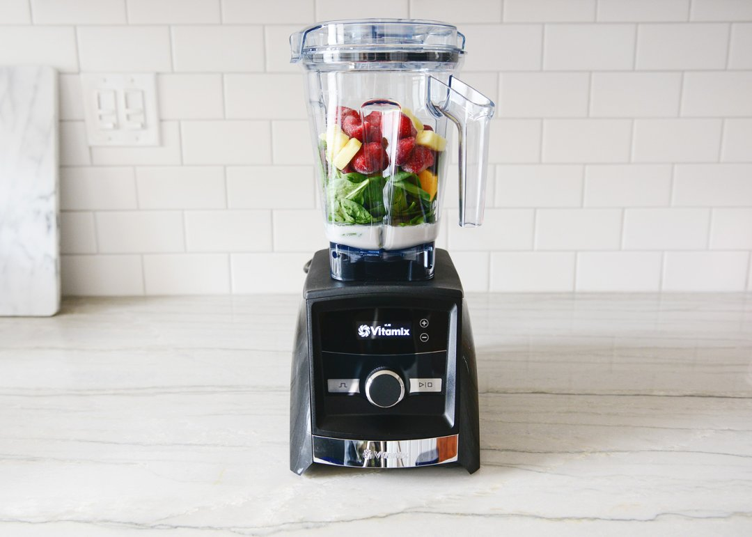 Fruit, spinach, and milk in blender ready to go