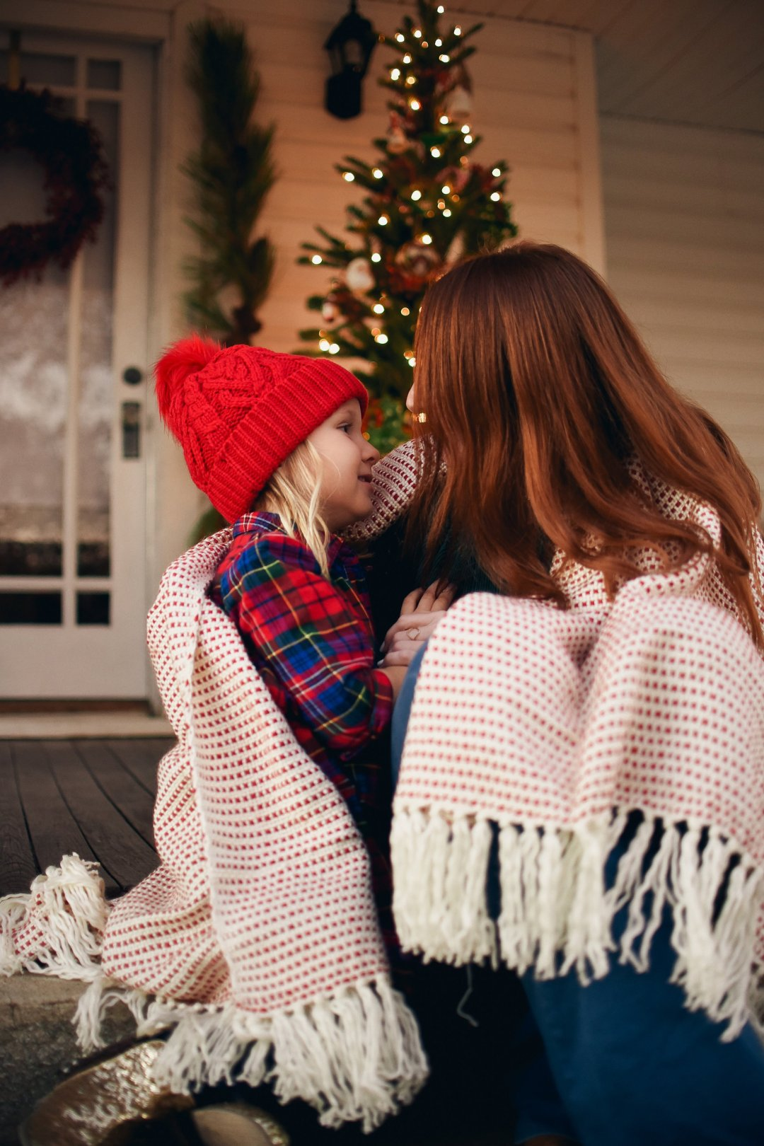 Mother and daughter cuddling and talking under festive red and white throw blanket in front of Christmas tree on front porch