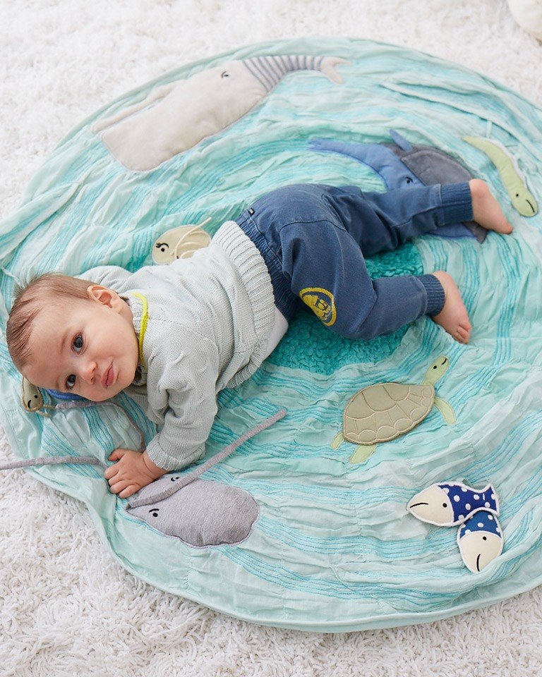 Baby playing on an under the sea themed activity mat.