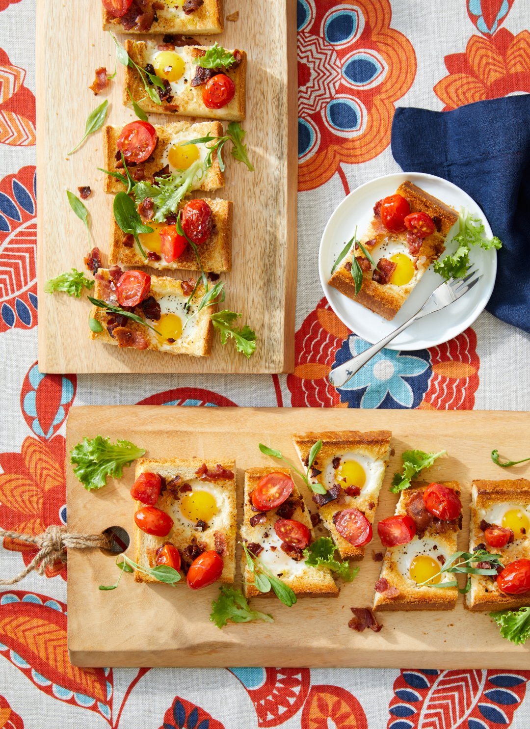 Open-faced tomato, egg and bacon tartine on a sliced baguette on two wood serving boards